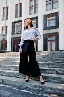 白いブラウス、広い黒いズボン、巨大な白い建物と彼女の手で黒いラップトップで階段でポーズ古典的なハイヒールの完璧な若い女性の肖像画