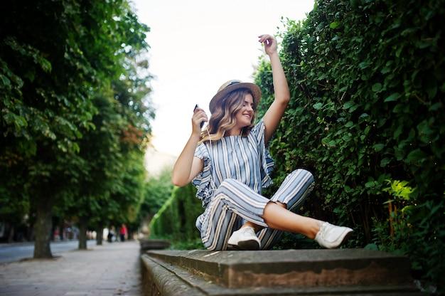 公園に座って、イヤホンをつけて音楽を聴くストライプの全体で見事な若い女性の肖像画。