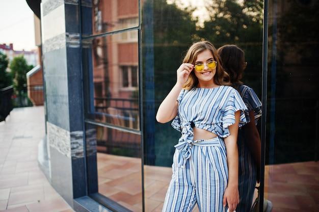バルコニーでストライプの全体と黄色のサングラスポーズを着て完璧な若い女性の肖像画