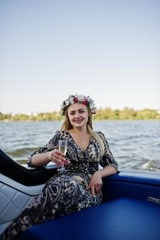 シャンパン編パーティーでヨットの上に座って花輪のブロンドの女の子。