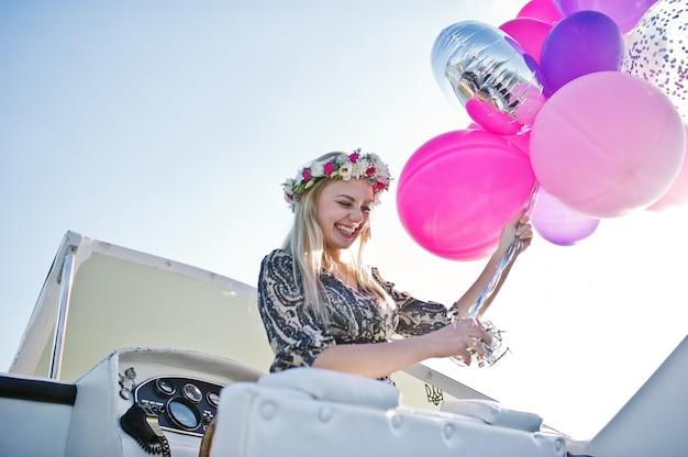 編パーティーでヨットの上に座って花輪のブロンドの女の子。