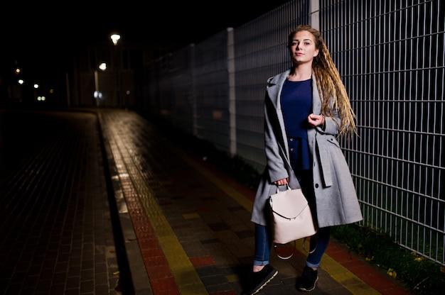街の夜の通りを歩いてドレッドヘアを持つ少女。