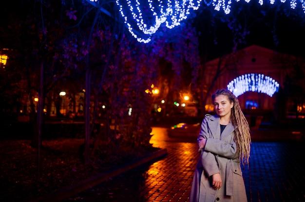 ガーランドライトに対して街の夜の通りを歩いてドレッドヘアを持つ少女。