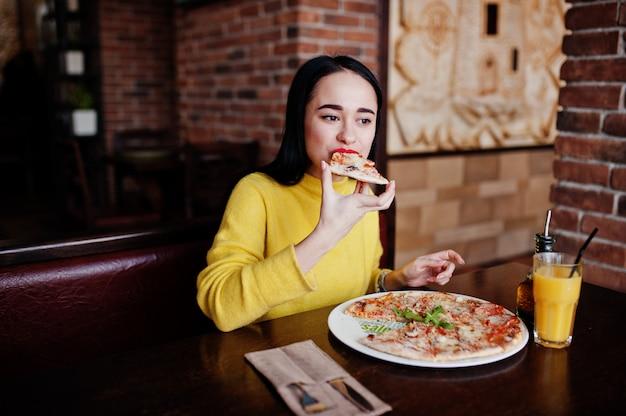 レストランでピザを食べて黄色のセーターで面白いブルネットの少女。