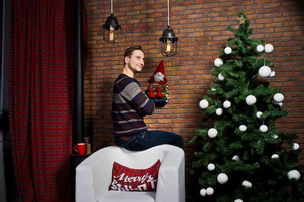 装飾と偽物のクリスマスツリーに対する男の肖像。