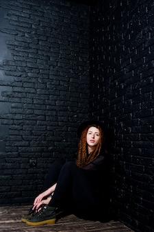 ドレッドとレンガの背景に帽子と黒の少女のスタジオ撮影。