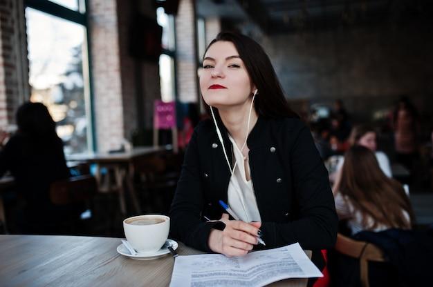 Девушка брюнет сидя на кафе с чашкой капучино, слушая музыкой на наушниках и пишет некоторые документы.