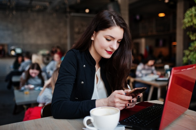カプチーノのカップでカフェに座って、赤いノートパソコンでの作業と携帯電話を見てブルネットの少女。