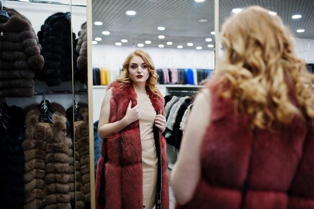 毛皮のコートと革のジャケットの店で毛皮のコートで優雅なブロンドの女の子。