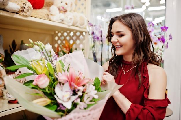 Брюнетка девушка в красном купить цветы в цветочном магазине.