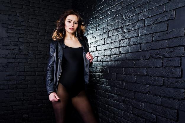 Портрет студии сексуальной девушки брюнет в черной кожаной куртке против кирпичной стены.