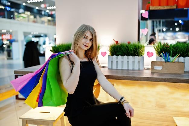 椅子に座ってモールで買い物袋を持つ少女。