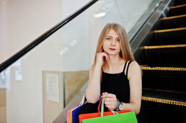 エスカレーターでショッピングモールで買い物袋を持つ少女。