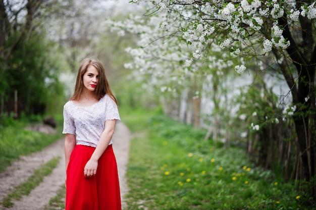 Портрет красивой девушки с красными губами в весеннем цветущем саду, платье на красном платье и белая блузка