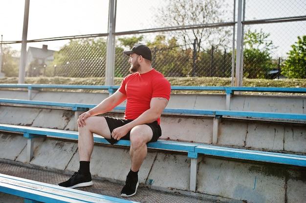 赤いシャツ、ショートパンツ、スタジアムでキャップの若いひげを生やした筋肉男着用