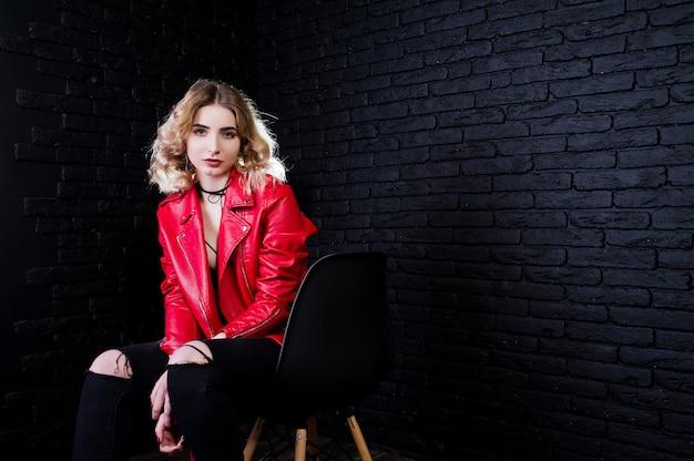 Портрет блондинка в красной кожаной куртке на стуле против кирпичной стены.