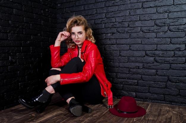 Портрет блондинка с красной шляпе, очках и кожаной куртке, на фоне кирпичной стены.