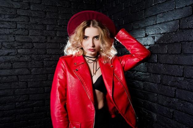 Портрет блондинка в красной шляпе и кожаной куртке против кирпичной стены.