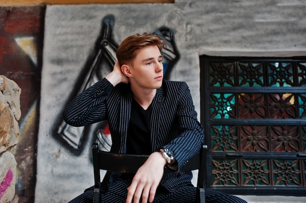 黒いジャケットのスタイリッシュな若いマッチョな少年が通りの屋外でポーズをとった。理髪店の落書きの壁に座って驚くべきモデル男。