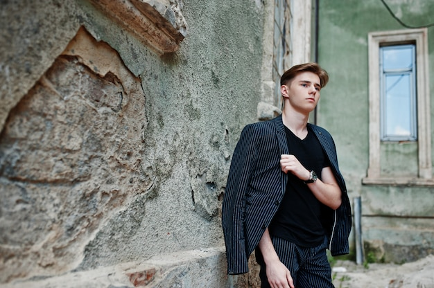 Молодой стильный мачо в черной куртке ставил открытый улицы. удивительная модель человека.