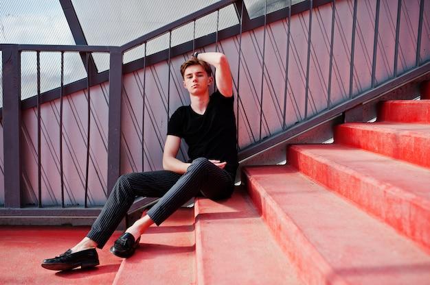 黒いジャケットのスタイリッシュな若いマッチョな少年が通りの屋外でポーズをとった。赤い階段のトンネルで驚くべきモデル男。
