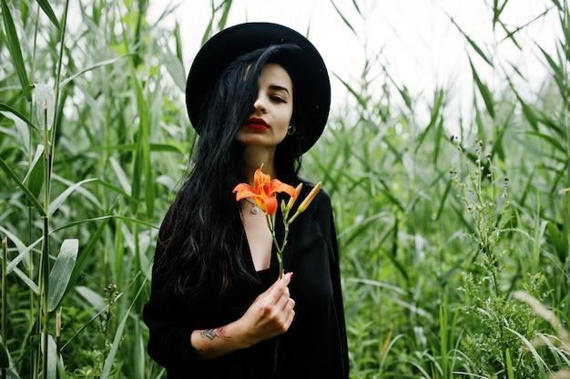 黒、赤い唇と帽子の官能的な女の子。ゴスの劇的な女性は、一般的なリードにオレンジ色のユリの花を保持します。