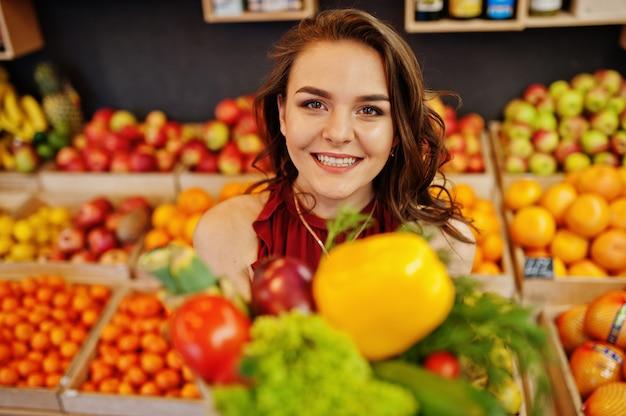 Девушка в красном цвете держа различные овощи на магазине плодоовощей.