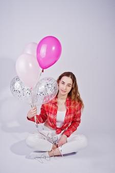 Молодая девушка в красной клетчатой рубашке и белых штанах с воздушными шарами