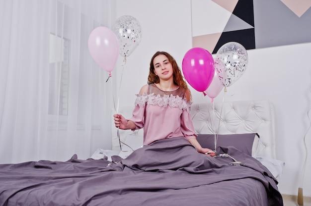 Молодая девушка с воздушными шарами на кровати