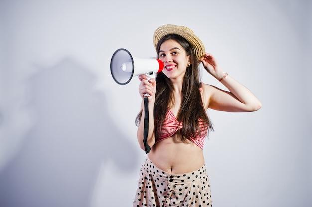Портрет великолепной молодой девушки в купальнике и шляпе говорит в мегафон