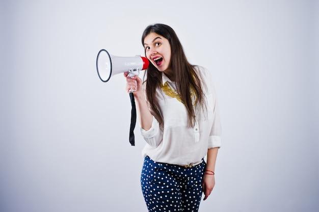 Портрет молодой женщины в синих брюках и белой блузке позирует с мегафоном