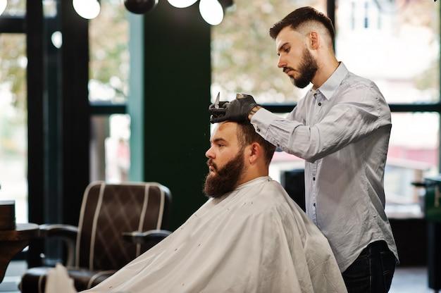 理髪店、職場で理容室でハンサムなひげを生やした男。