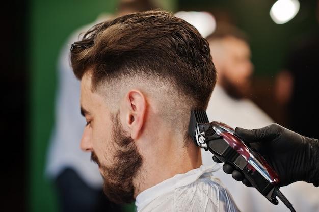 理髪店、職場で理容室でハンサムなひげを生やした男。うなじを閉じます。