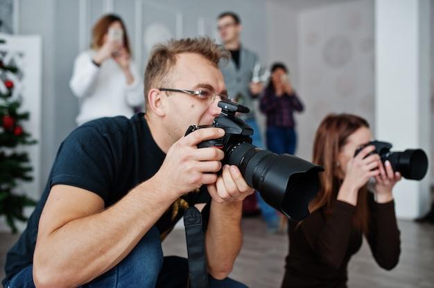 Команда из двух фотографов снимает на студии позади еще трех рабочих. профессиональный фотограф на работе. мастер класс.