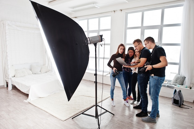Фотограф объясняет о съемке своей команде в студии и смотрит на ноутбук. разговаривает со своими помощниками с фотоаппаратом во время фотосессии. работа в команде и мозговой штурм.
