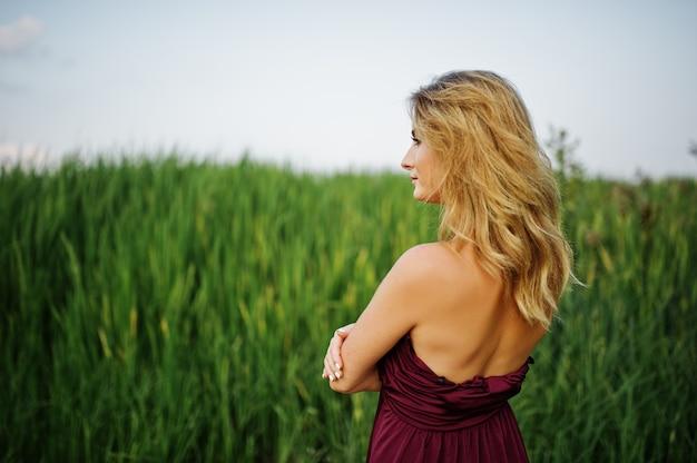 Блондинка чувственная женщина в красном платье марсала позирует в камышах.