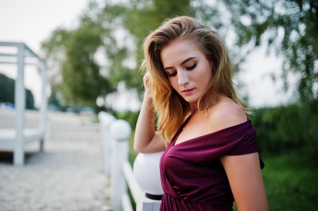 リゾートのビーチでポーズをとって赤いマルサラドレスで金髪の官能的な女性。