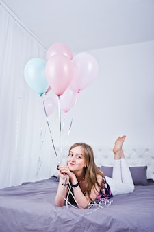 Счастливая девушка с цветными шарами на кровати в номере. празднование дня рождения тема.
