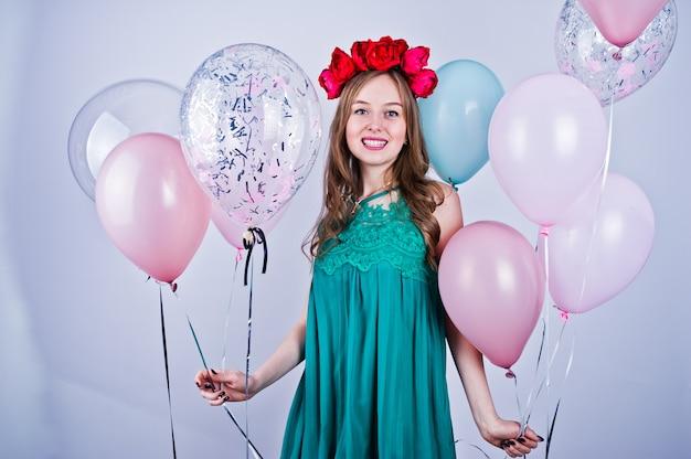 緑のターコイズドレスと白で隔離される色の風船と花輪で幸せな女の子。誕生日のテーマを祝います。