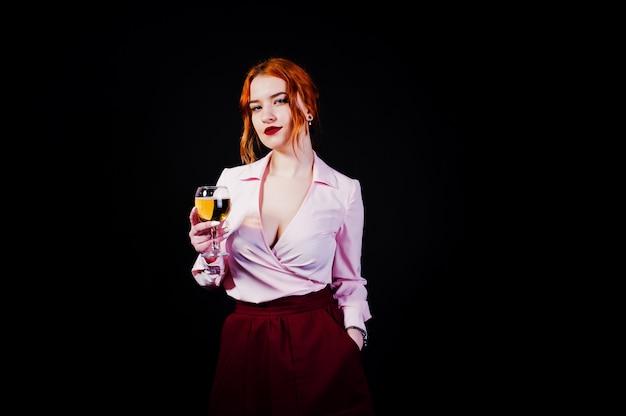 Шикарная красная с волосами девушка в розовой блузке и красной юбке с бокалом вина под рукой изолированной на черноте.