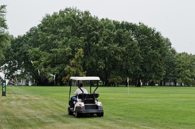 ゴルフ場でゴルフ車を運転する男。