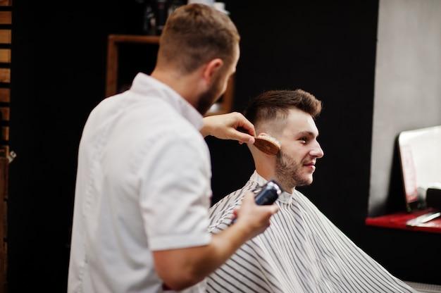 Молодой бородатый человек получая стрижку парикмахером пока сидящ в стуле на парикмахерскае. парикмахерская душа.