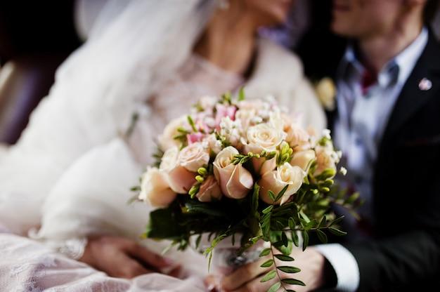 素晴らしい結婚式のカップルのポーズと車の中でキス。