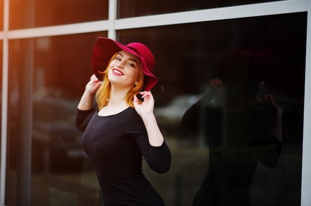 Модная рыжеволосая девушка в розовой шляпе и черном платье с ярким макияжем на большом окне