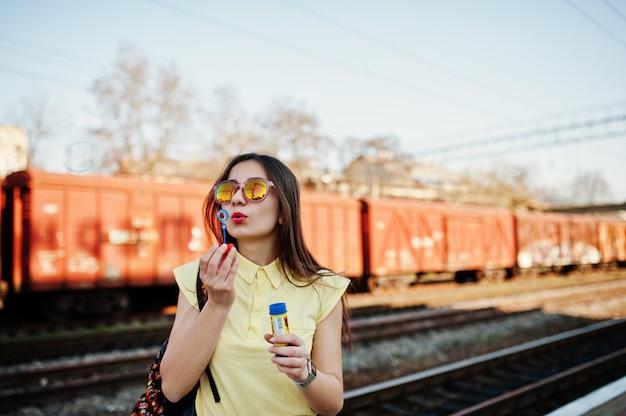 Молодая девушка, стоя на платформе на вокзале и дует мыльные пузыри, носить желтую футболку, джинсы и солнцезащитные очки, с рюкзаком.