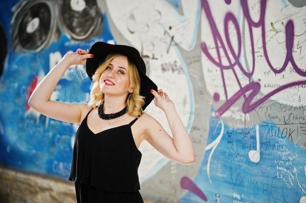 黒のドレス、ネックレス、落書きの壁に帽子の金髪の女性。
