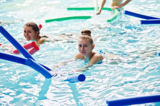 Фитнес-группа девушек, делающих аэробные упражнения в бассейне в аквапарке.