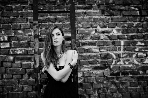 Красная с волосами панк-одежда женщины на черном платье на крыше против кирпичной стены с железной лестницей.