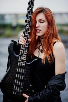 赤髪のパンクの女性は、屋根でベースギターと黒に着用します。