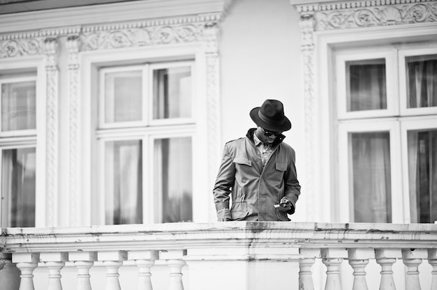 緑のコートのマントと黒い帽子の黒人アフリカ系アメリカ人のファッションの肖像画は、黄色の大邸宅のバルコニーに滞在します。白黒写真